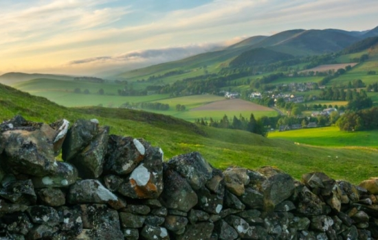 Countryside view with stone wall in the front and rolling hills behind.