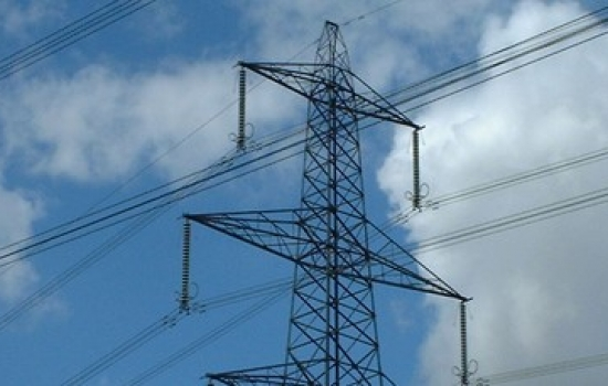 Electricity pylon outside with a blue sky and white clouds behind