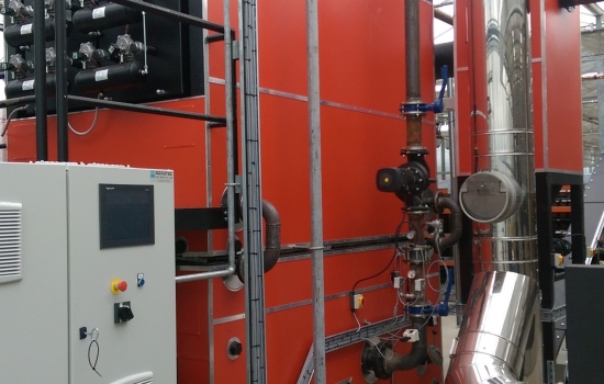 Large red biomass boiler with sliver pipes in a greenhouse