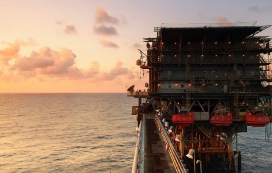 oil rig in the ocean with a sunset