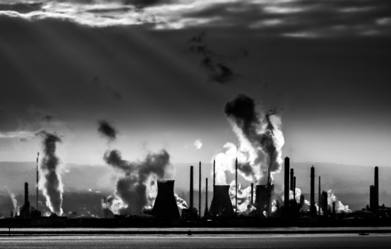 A black and white outline of a factory with smoke