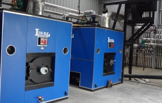two blue biomass boilers in a shed