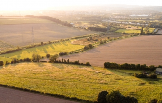 Rolling countryside fields with grass and crops