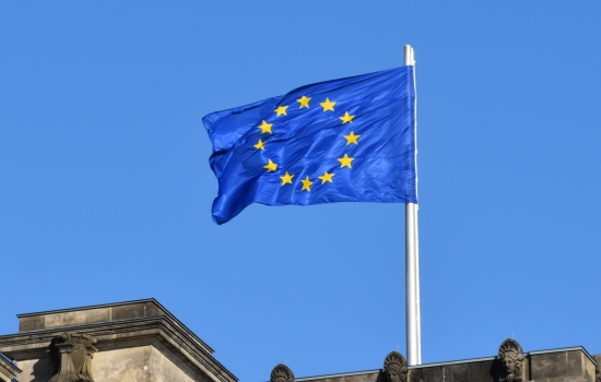European flag flying above a building with a blue sky background