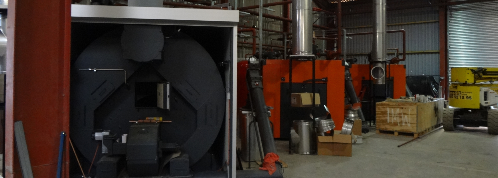 Three biomass boilers being installed in a shed