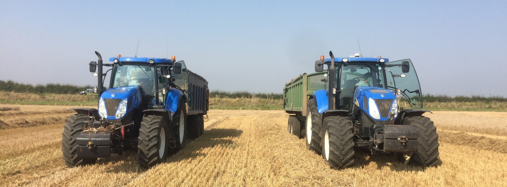 Two blue tractors in a field of straw