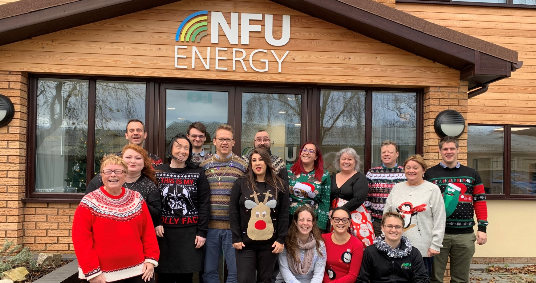 Staff in Christmas Jumpers outside the front of the office