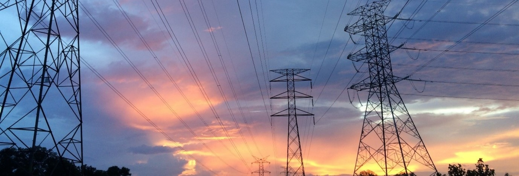 Electricity pylons with a sunset in the background