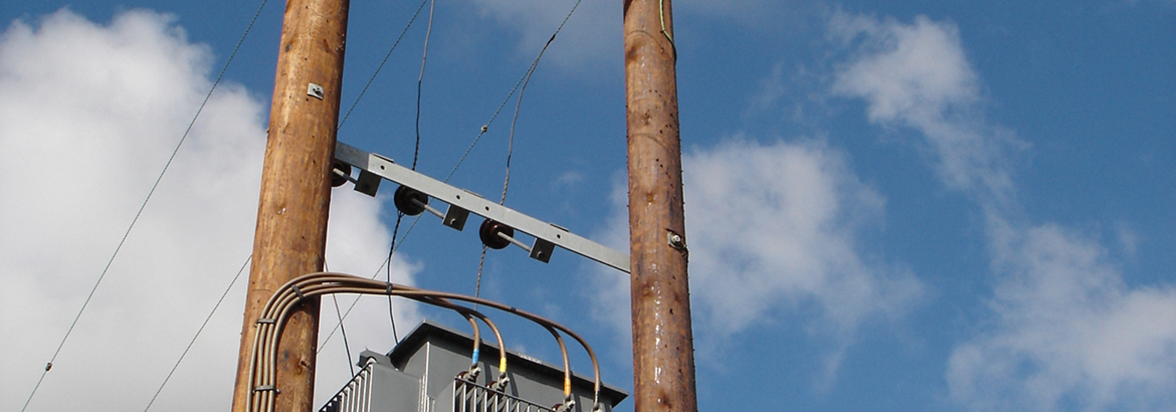 Electricity transformer on overhead poles representing NFU Energy's connections planning service